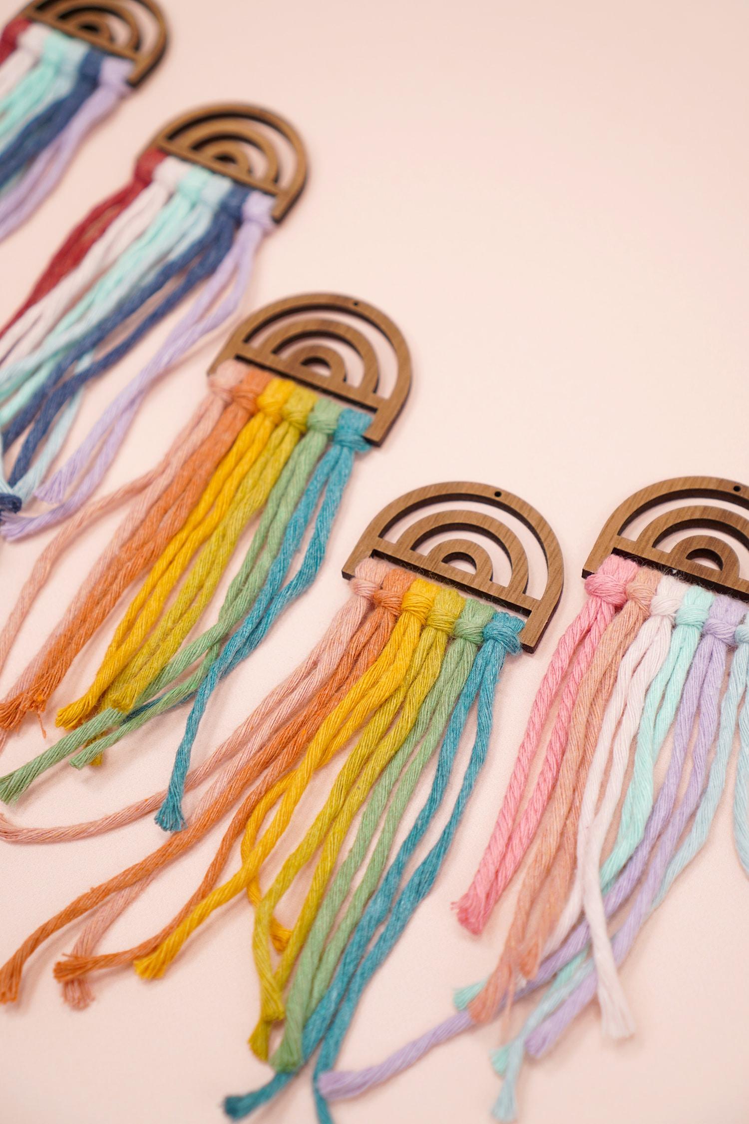 Assorted untrimmed rainbow macramé earrings on peach background