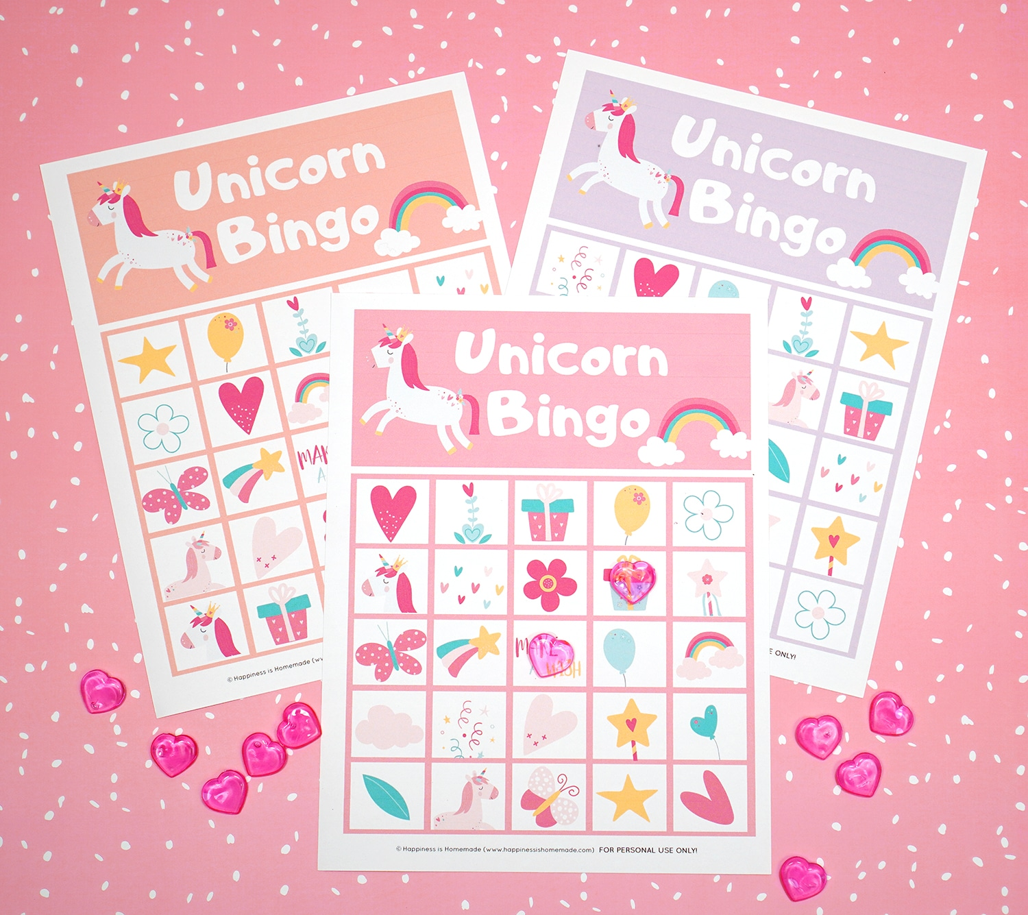 Printable Unicorn Bingo Game Cards on pink background with pink heart markers