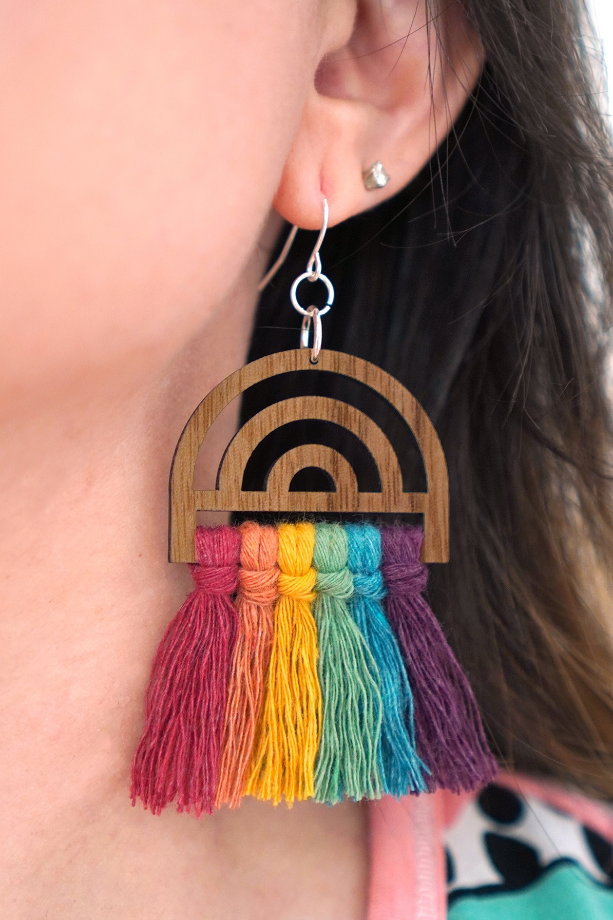 Close up or rainbow macramé earring being worn