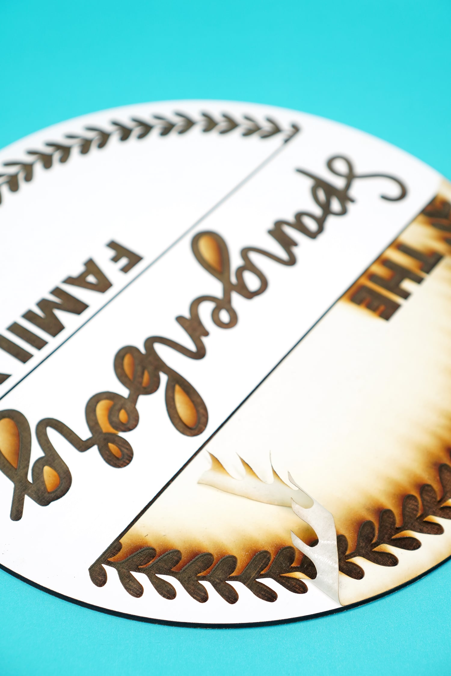 Removing Masking Tape from a Glowforge Engraved Sign on aqua background
