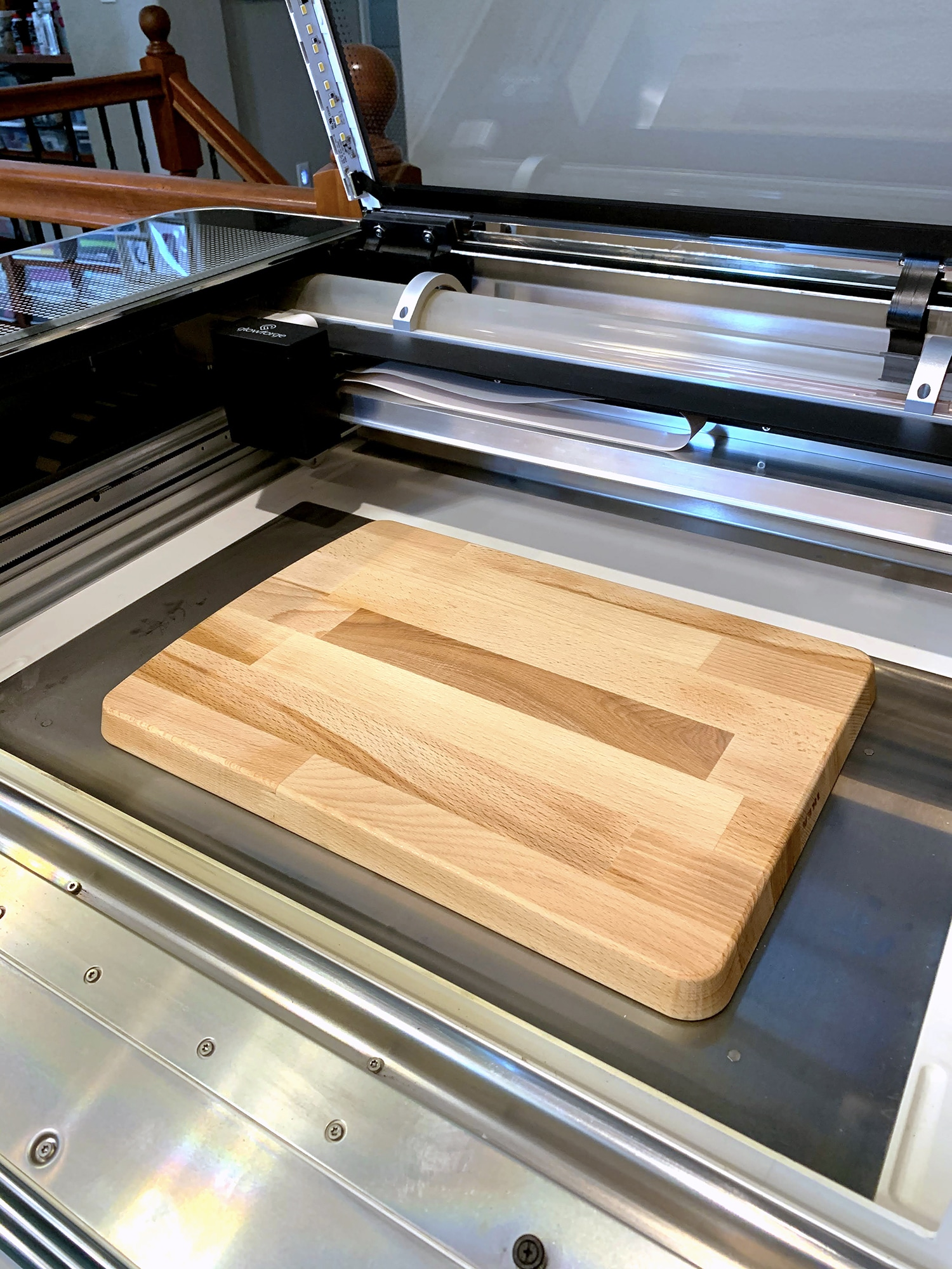 Glowforge machine with front dropped down and cutting board in base of machine