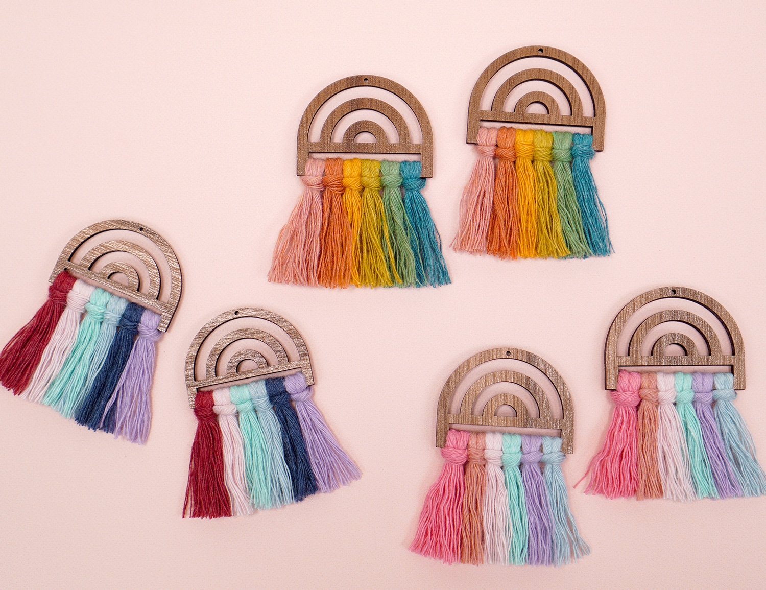 Three Assorted Pairs of Wooden Rainbow Macrame Earrings on Peach Background