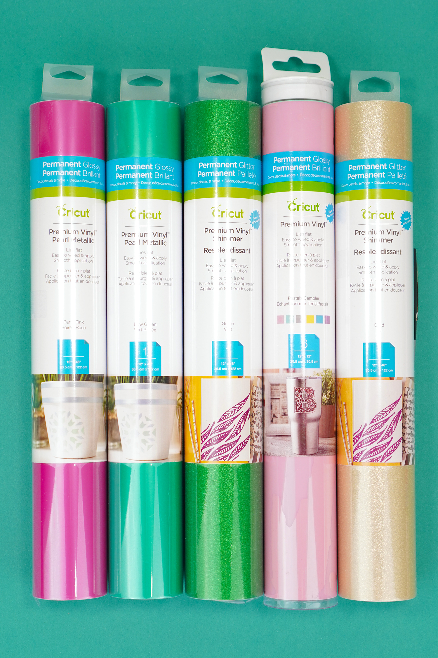Cricut Vinyl rolls in packaging - pink, teal, green, baby pink, and gold on teal background