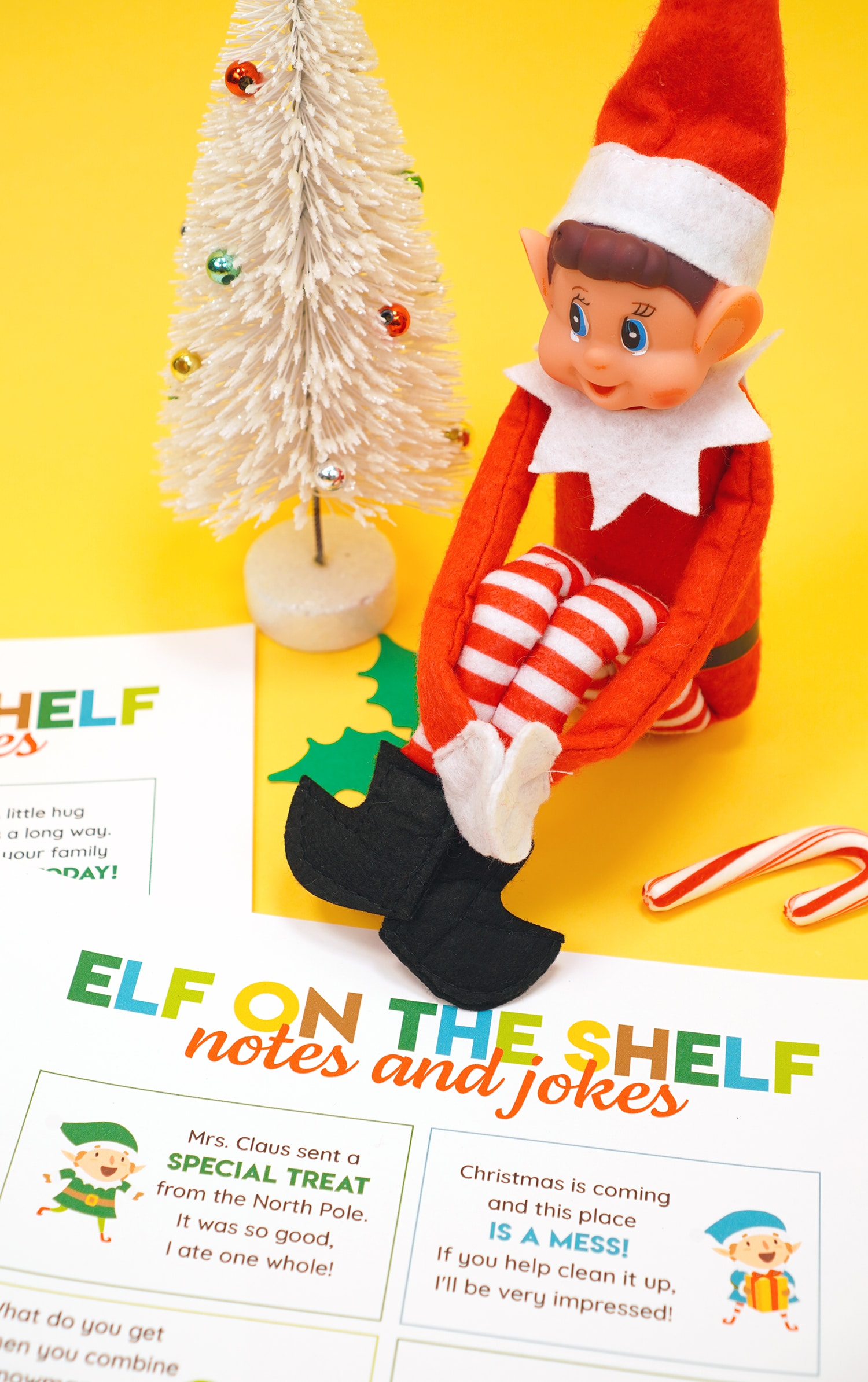 Elf doll on a yellow background with printed Elf on the Shelf note and joke cards and candy canes and Christmas decorations in the background.