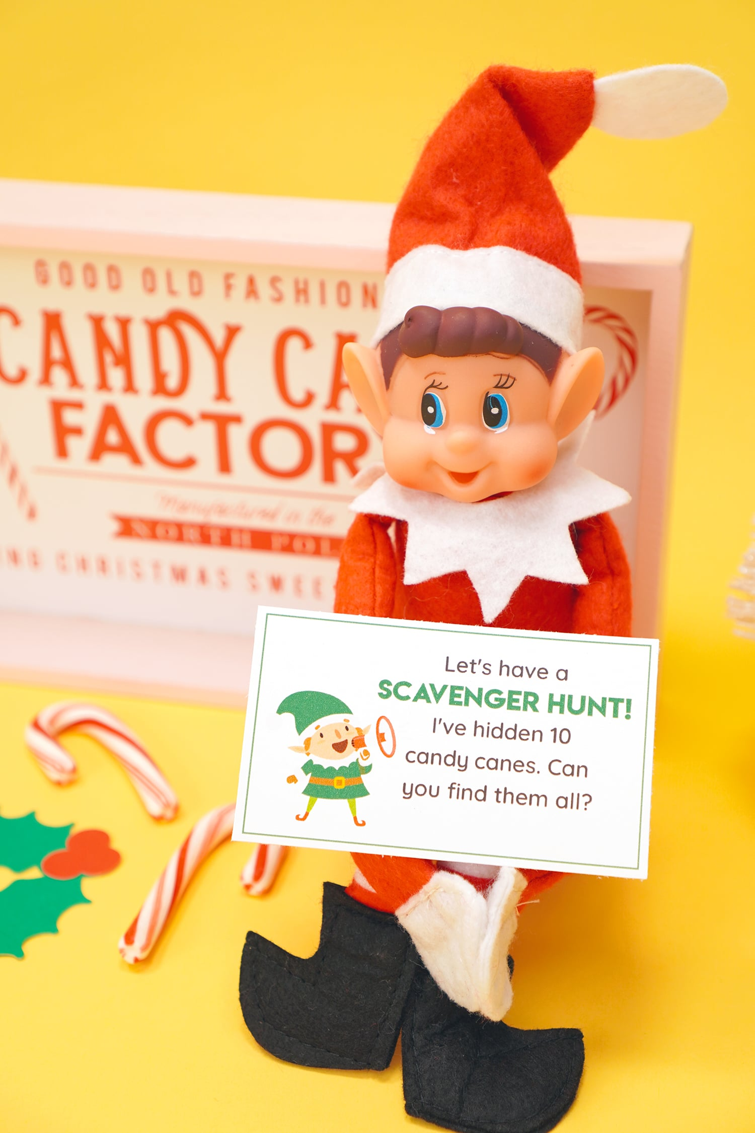 Elf doll on a yellow background holding a printed Elf on the Shelf scavenger hunt note card and candy canes and Christmas decorations in the background.