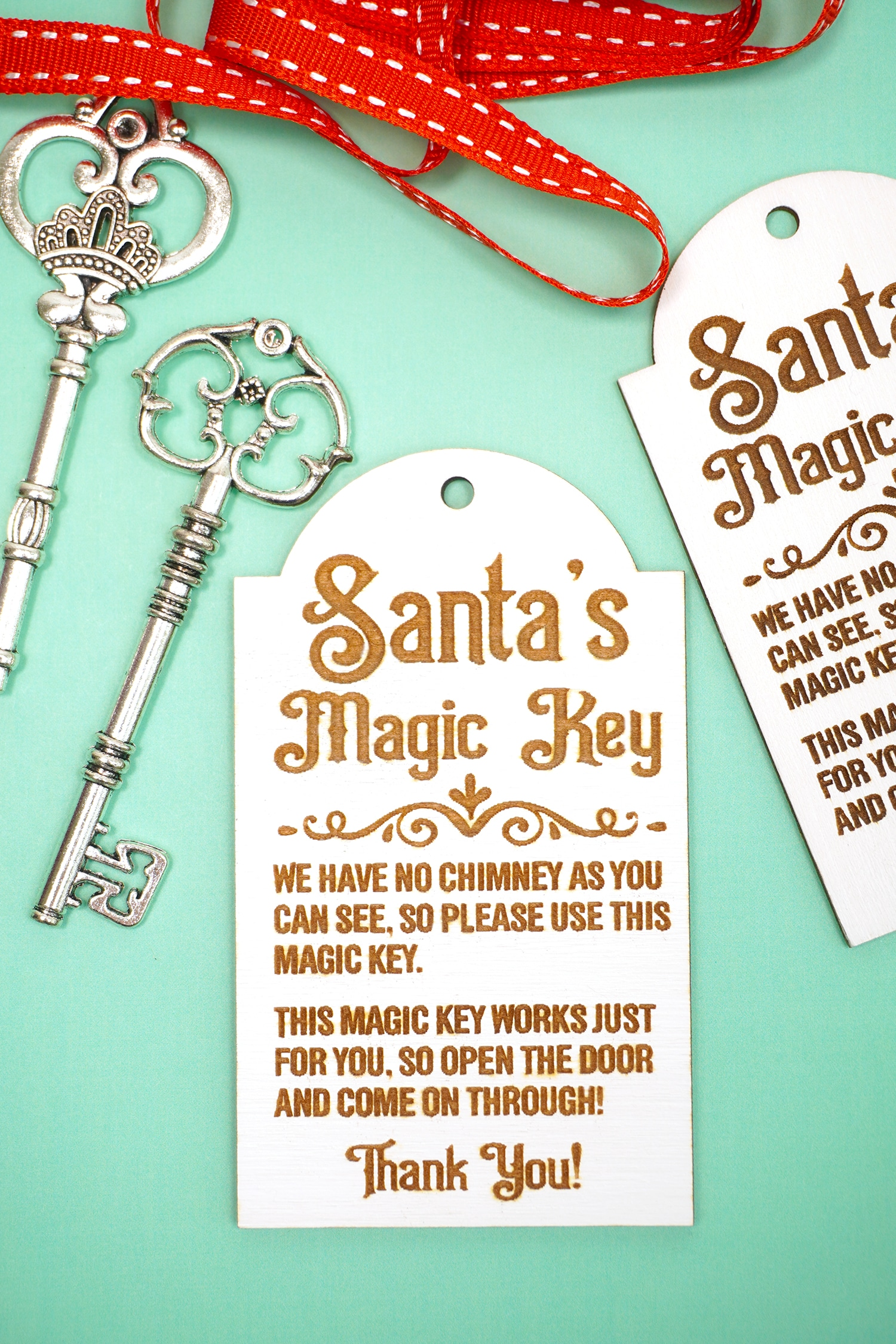 Laser engraved Santa's Magic Key wood tags with red ribbon and silver keys on a mint green background