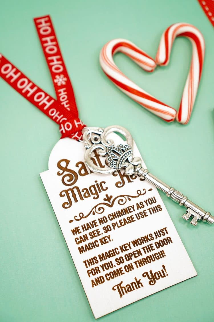 Santa's Magic Key laser engraved wood tag with red ribbon and silver key on a mint green background with candy canes