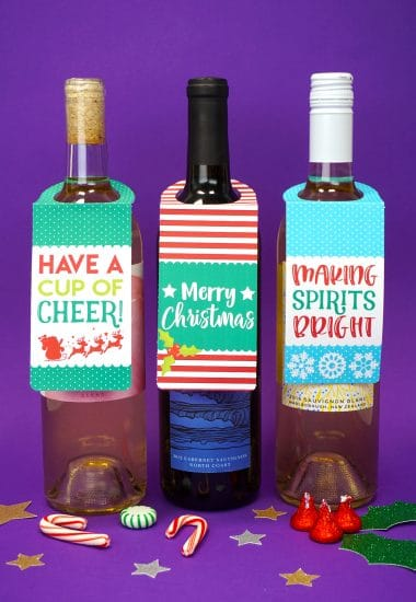 "Three bottles of wine on purple background with ""Have a Cup of Cheer"" and ""Merry Christmas"" and ""Making Spirits Bright"" printable Christmas wine bottle gift tags"