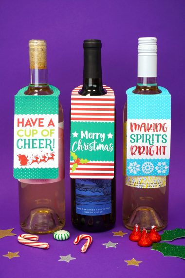 """Three bottles of wine on purple background with """"Have a Cup of Cheer"""" and """"Merry Christmas"""" and """"Making Spirits Bright"""" printable Christmas wine bottle gift tags"""