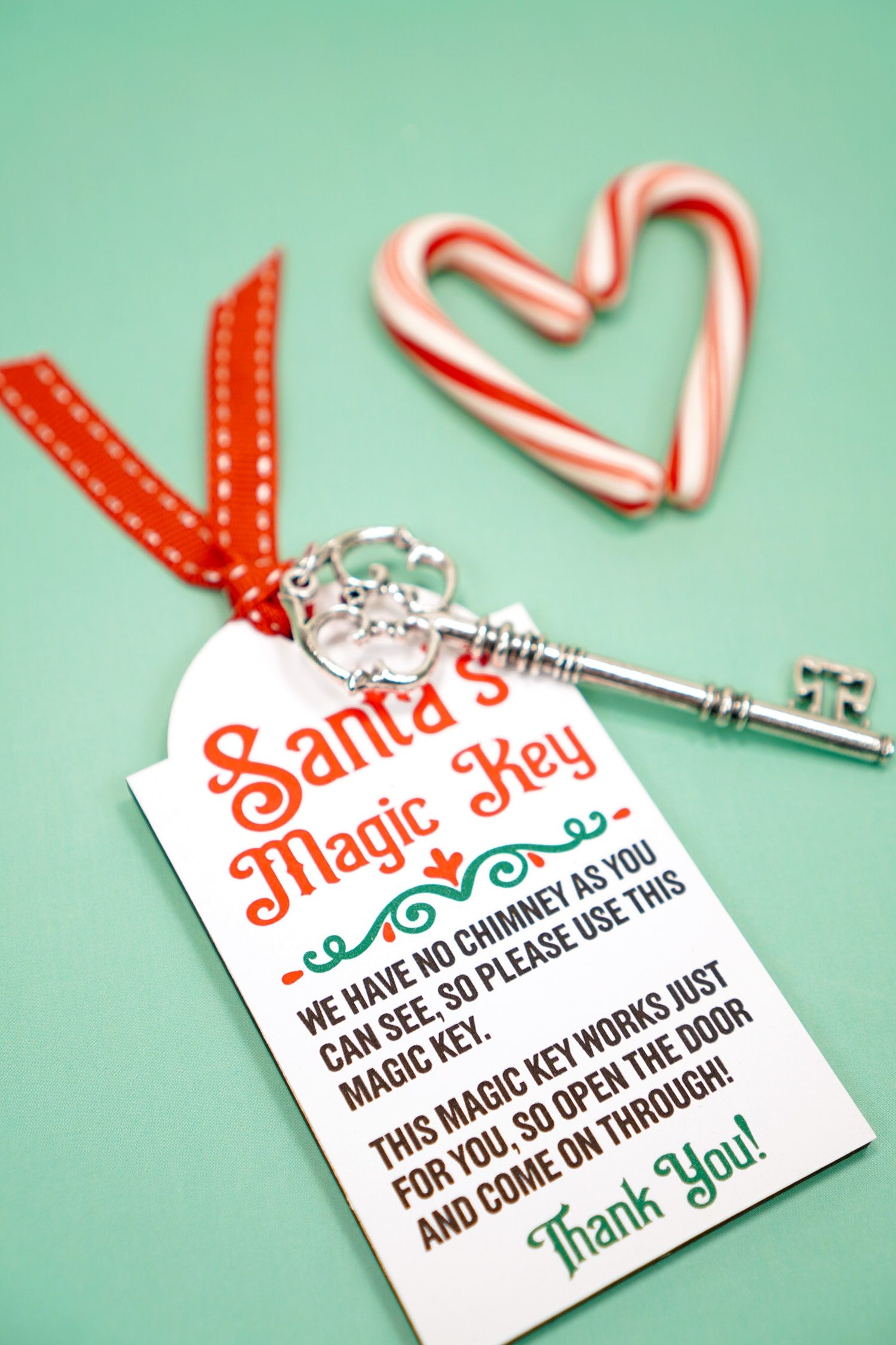 Santa's Magic Key printable tag with red ribbon and silver key on a mint green background with candy canes