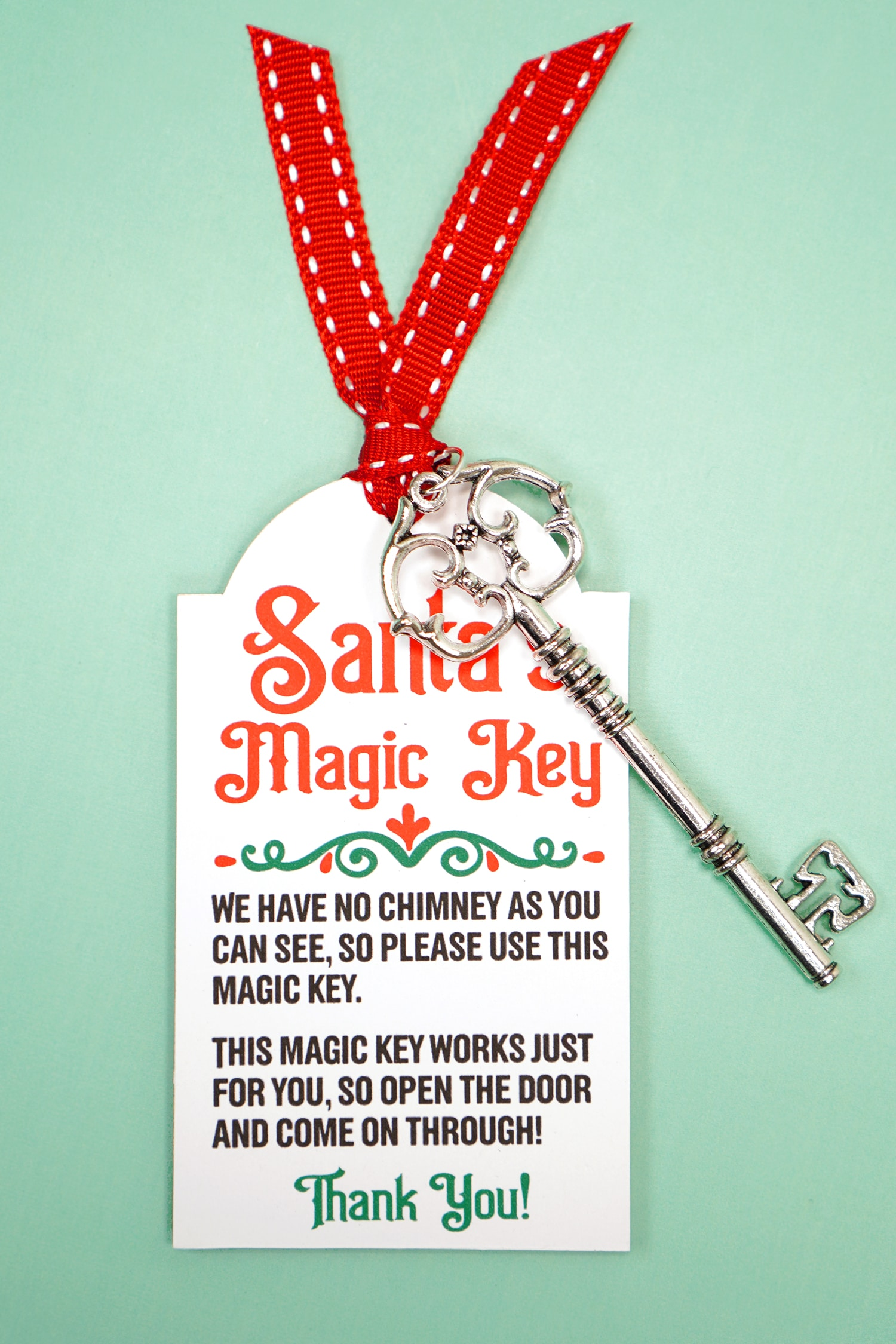 Santa's Magic Key printable tag with red ribbon and silver key on a mint green background