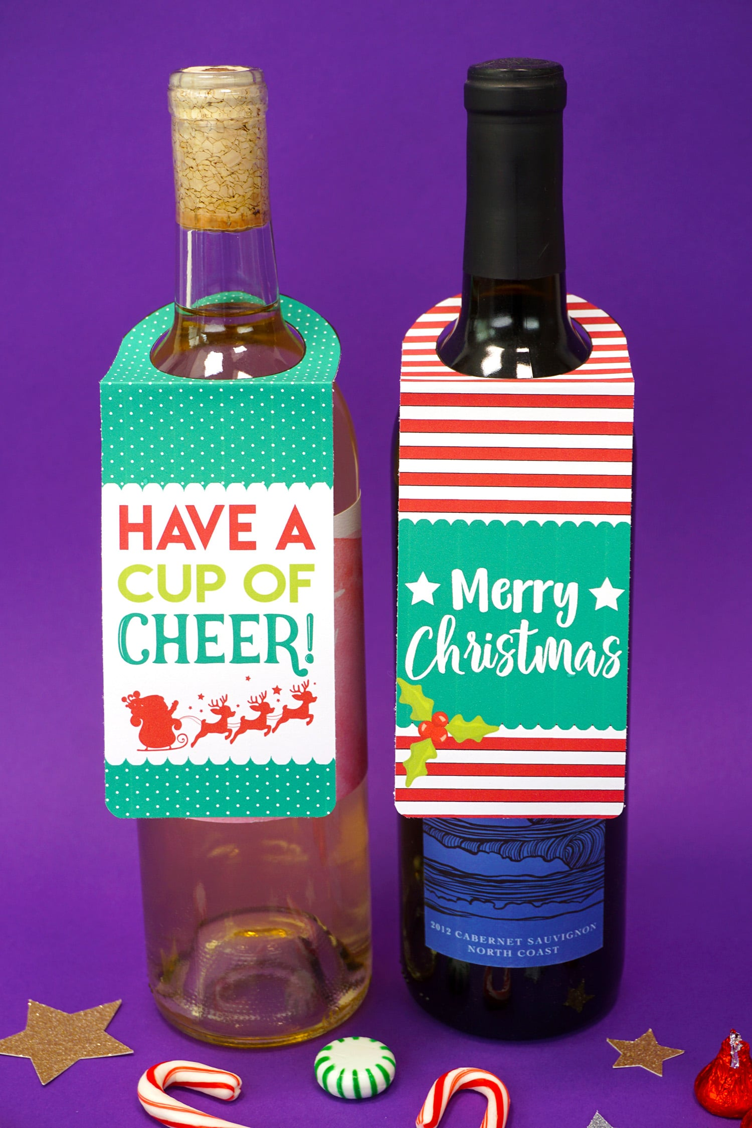 """Two bottles of wine on purple background with """"Have a Cup of Cheer"""" and """"Merry Christmas"""" printable Christmas wine bottle gift tags"""