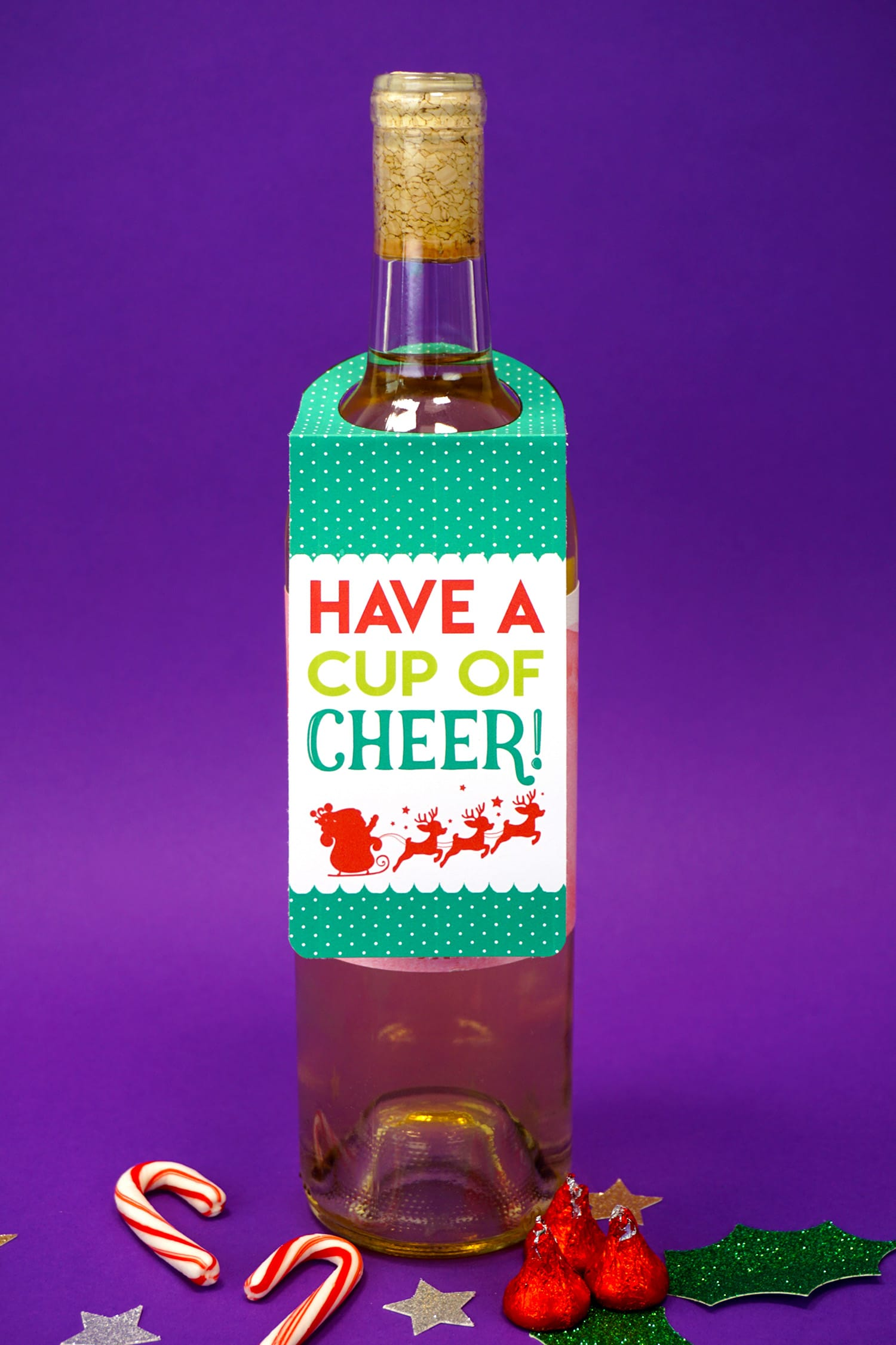 """""""Have a Cup of Cheer"""" red, green, and white """"Merry Christmas"""" red, white, and green Christmas wine tag on bottle on purple background with candy canes and stars"""