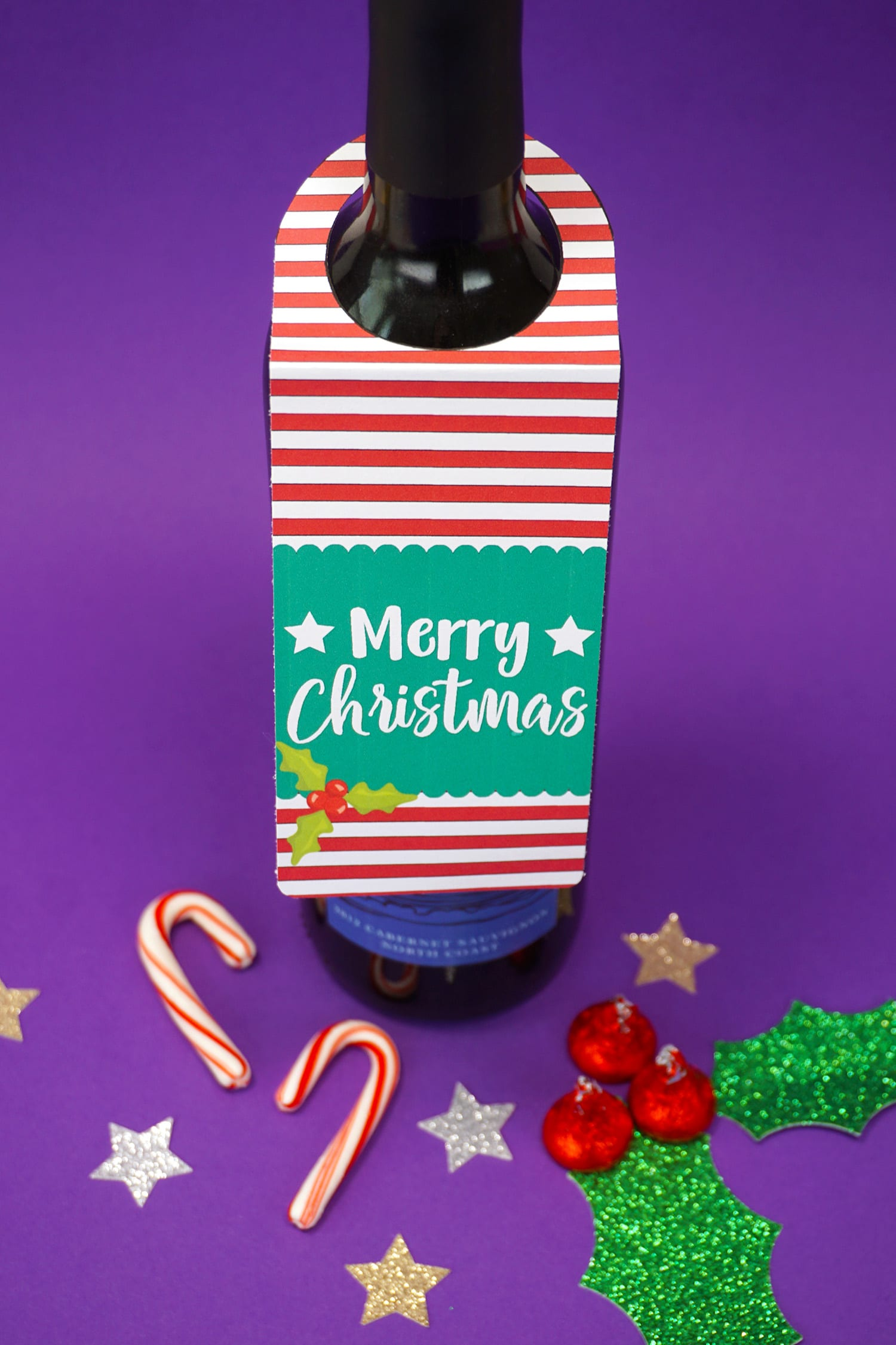 """""""Merry Christmas"""" red, white, and green Christmas wine tag on bottle on purple background with candy canes and stars"""