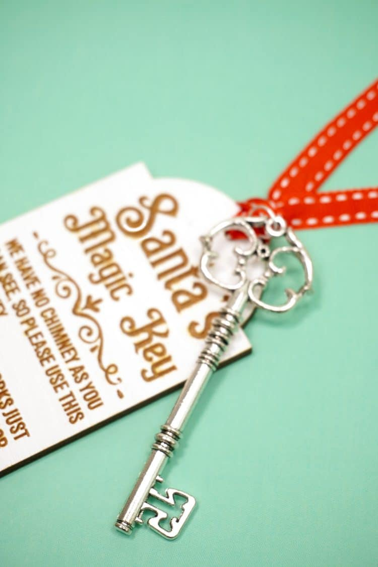 Closeup of silver key attached to a Santa's Magic Key tag with red ribbon on mint green background