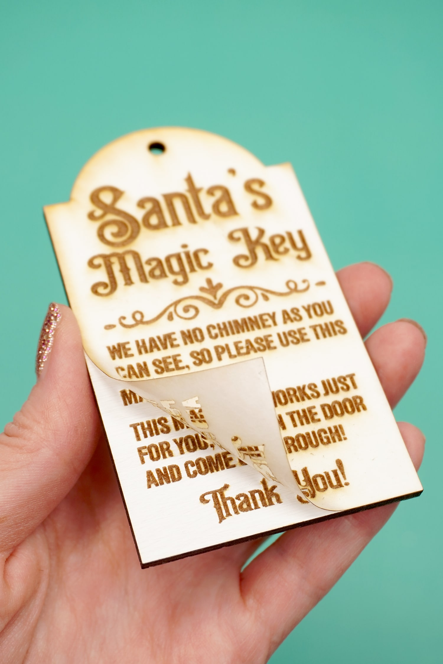 Peeling the masking from a laser engraved Santa's Magic Key wood tag