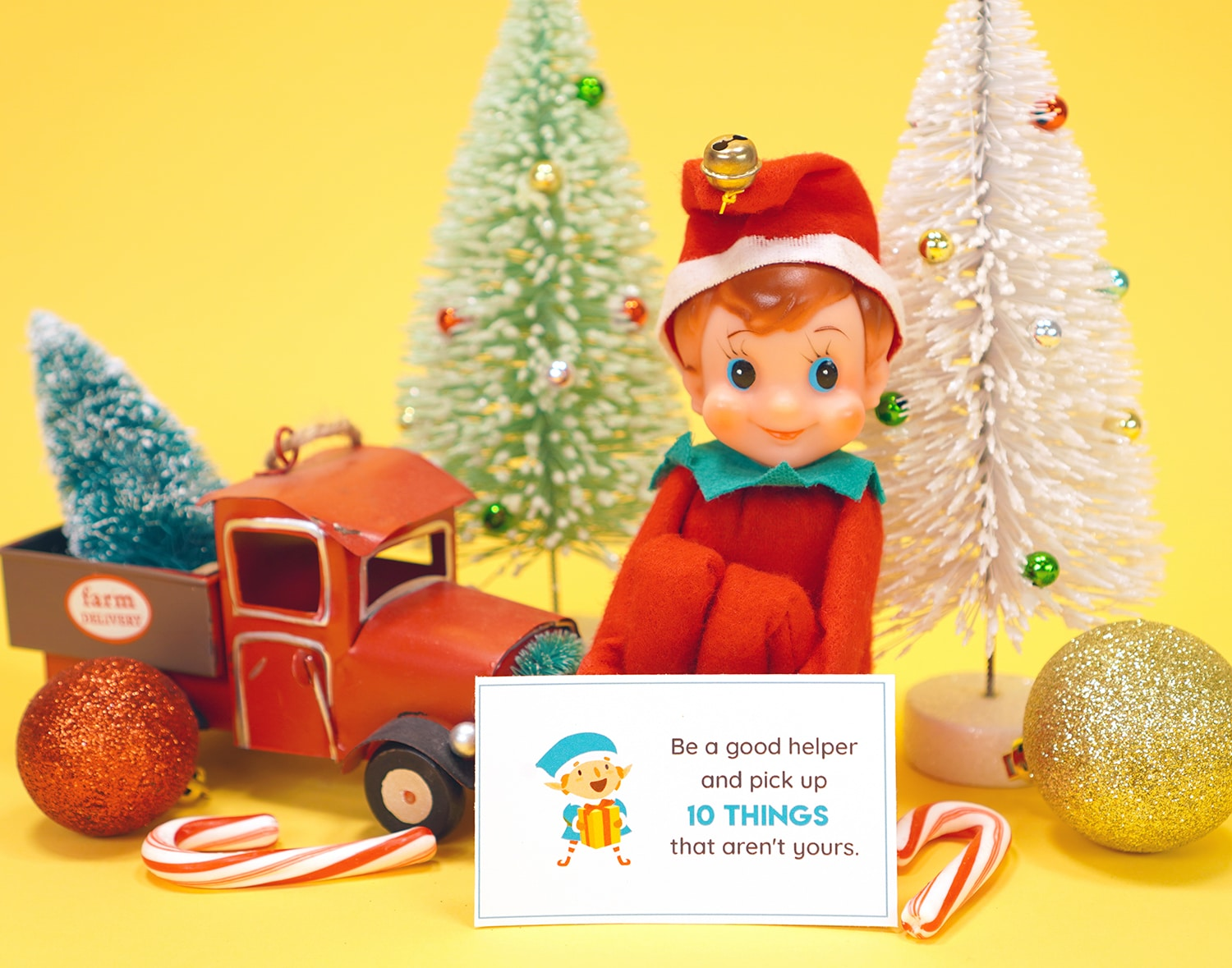 Vintage shelf sitter elf doll with Elf on the Shelf printable note card, candy canes, toy truck, ornaments, and Christmas decorations on yellow background