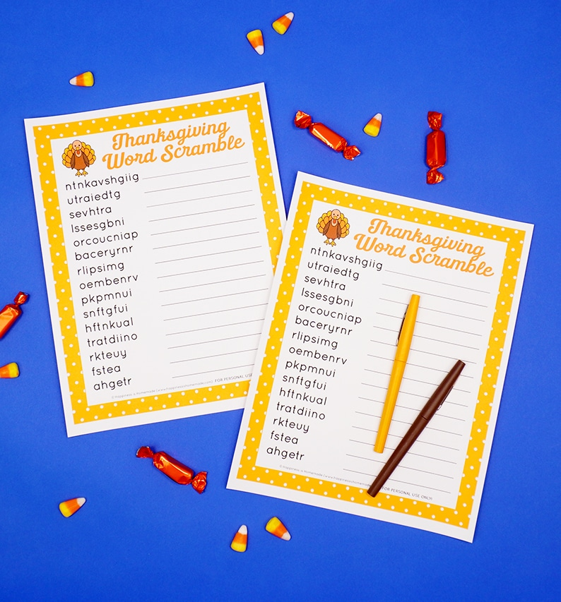 Two printable Thanksgiving Word Scrambles on a blue background surrounded by candy and a yellow and brown pen.