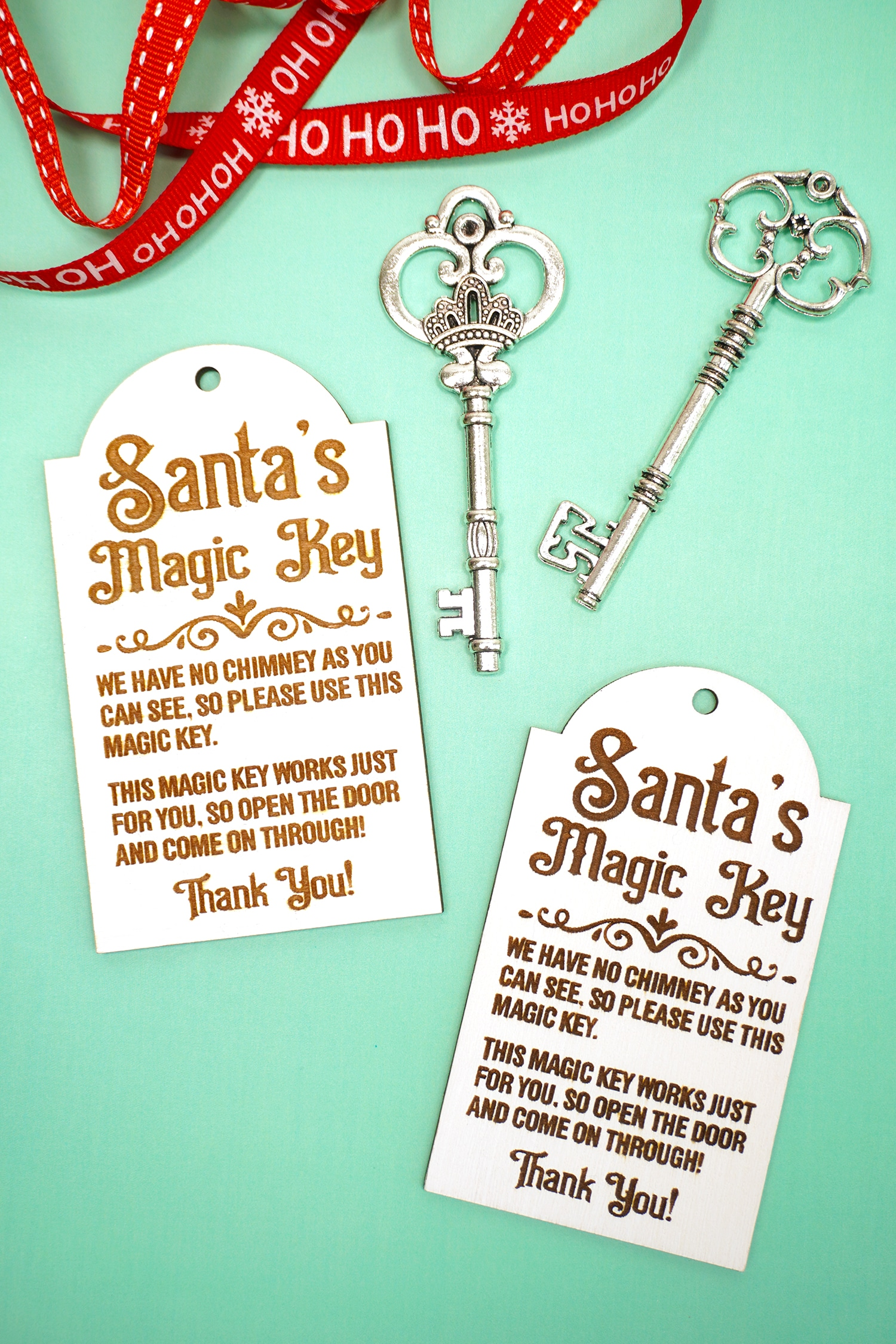Two Santa's Magic Key tags with red ribbons and silver keys on a mint green background