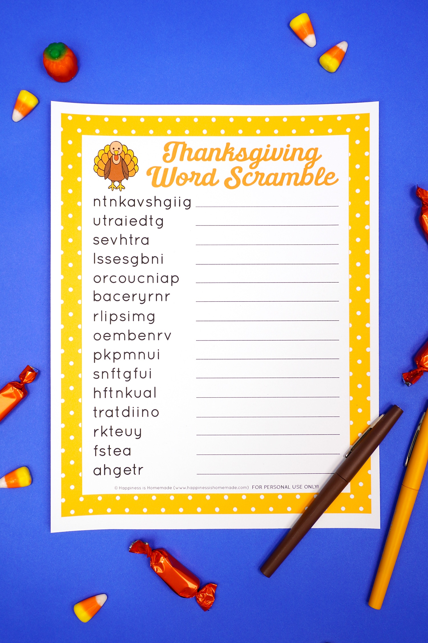 Printable Thanksgiving Word Scramble on a blue background surrounded by candy and a yellow and brown pen.