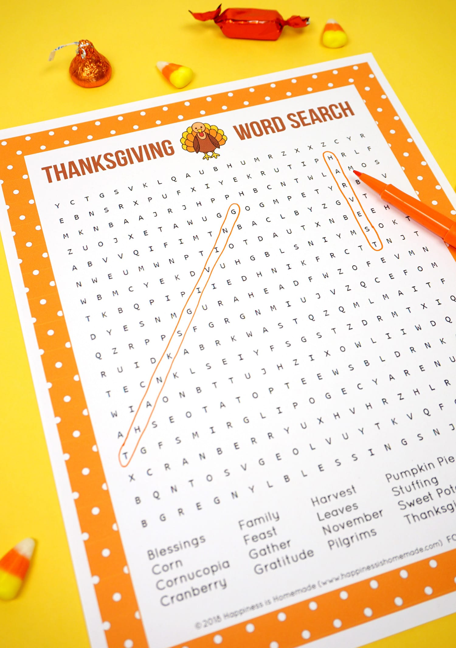 Two Printable Thanksgiving Word Search puzzle game on yellow background with orange pen and candy