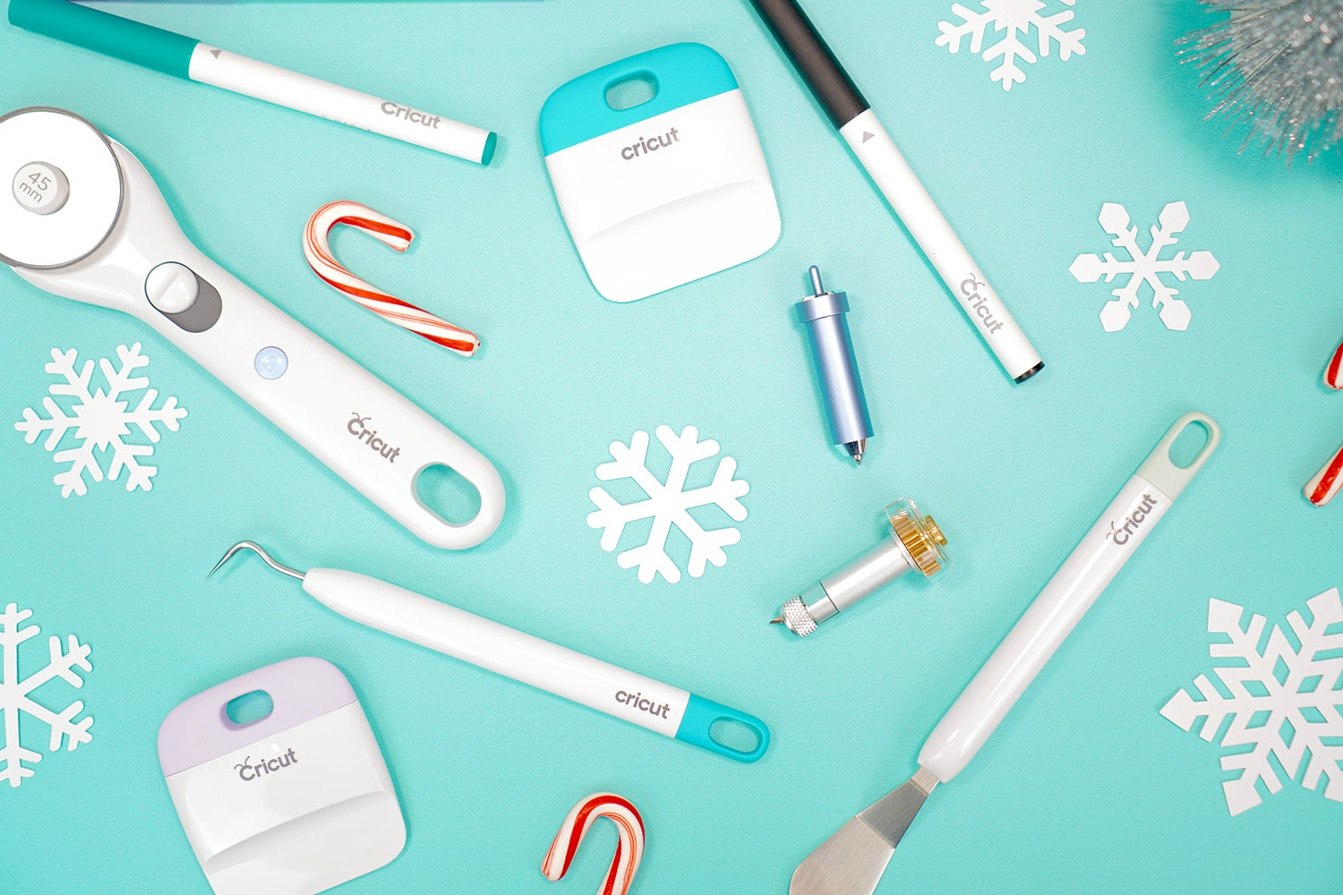 Scattered Cricut tools and accessories on aqua background with paper snowflakes and candy canes