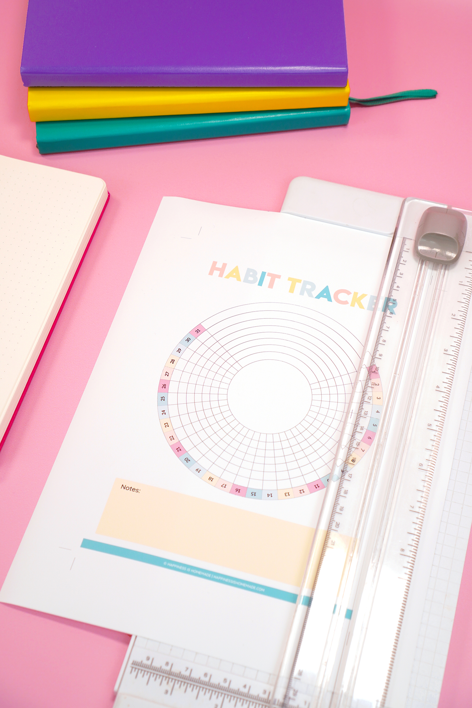 Printable Habit Tracker sheet in white paper cutter on pink background with bullet journals