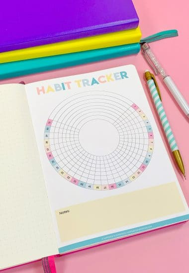 Printable Circle Habit Tracker in bullet journal on pink background with colorful pencils and stack of journals