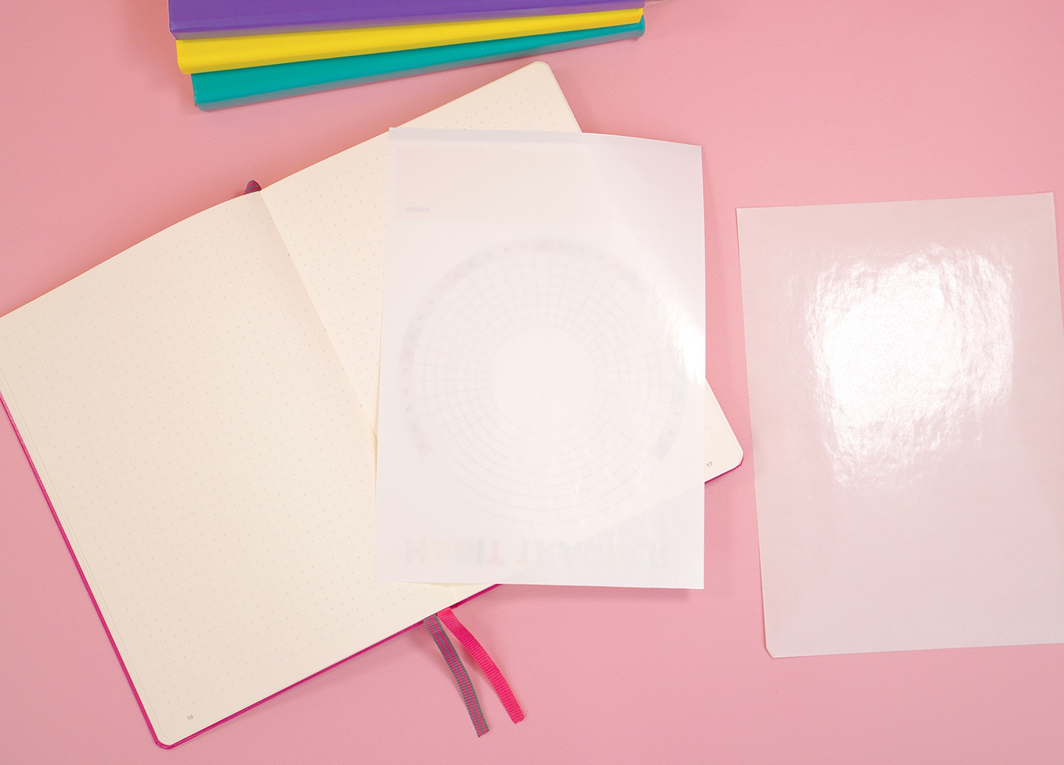 Open bullet journal on pink background with peeled sheet of sticker paper on top