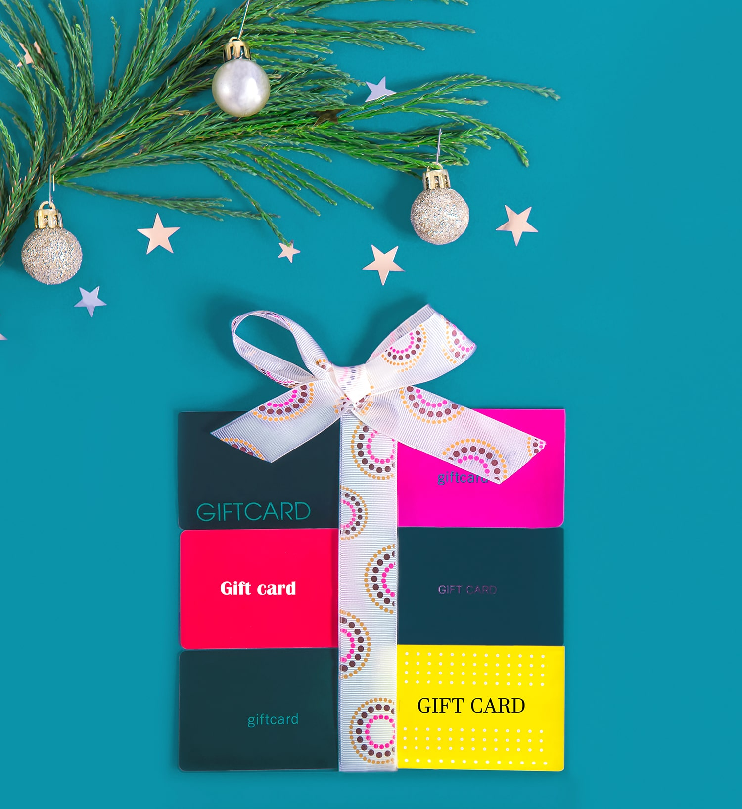 Flat lay gift box shape made of shop gift cards and tied with a ribbon on a blue background with Christmas tree branch