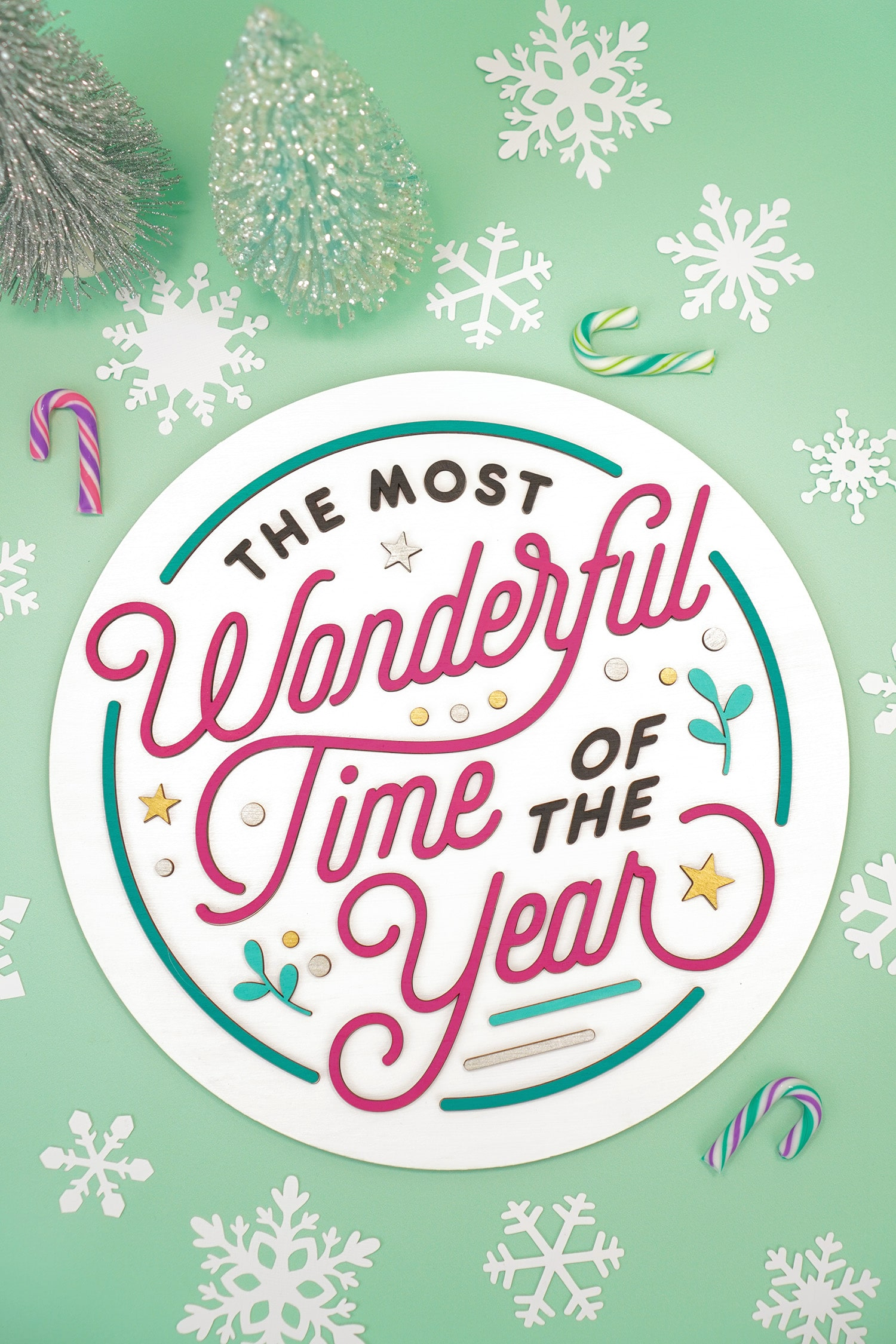 "Round layered 3D laser cut wood sign ""The Most Wonderful Time of the Year"" on mint green background with colorful candy canes, white paper snowflakes, and pastel glitter bottle brush trees"