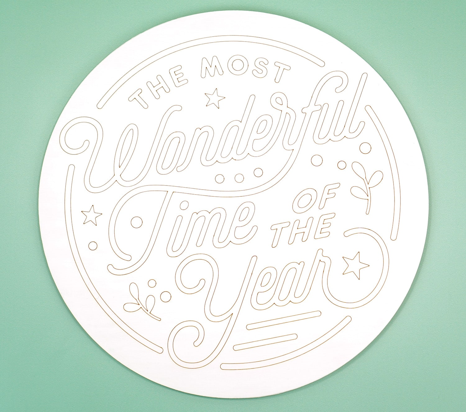 "Round white wood sign with ""The Most Wonderful Time of the Year"" scored into it with a Glowforge laser"