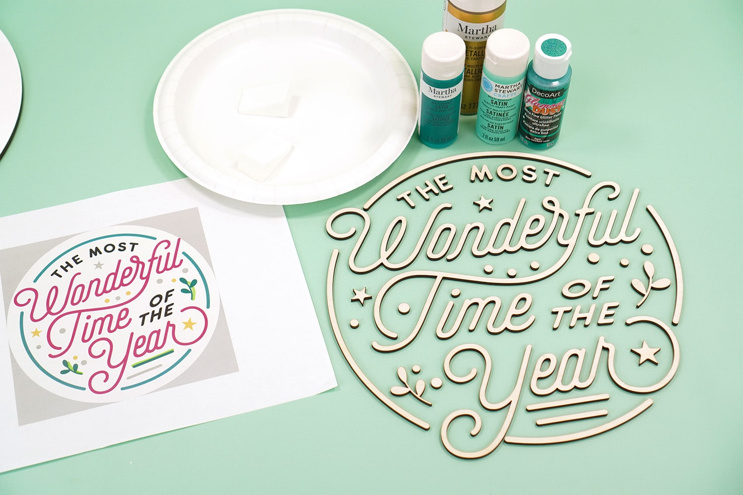 "Mint green background with ""The Most Wonderful Time of the Year"" Glowforge laser cut wood pieces, paint, and a print out of color palette on white paper"