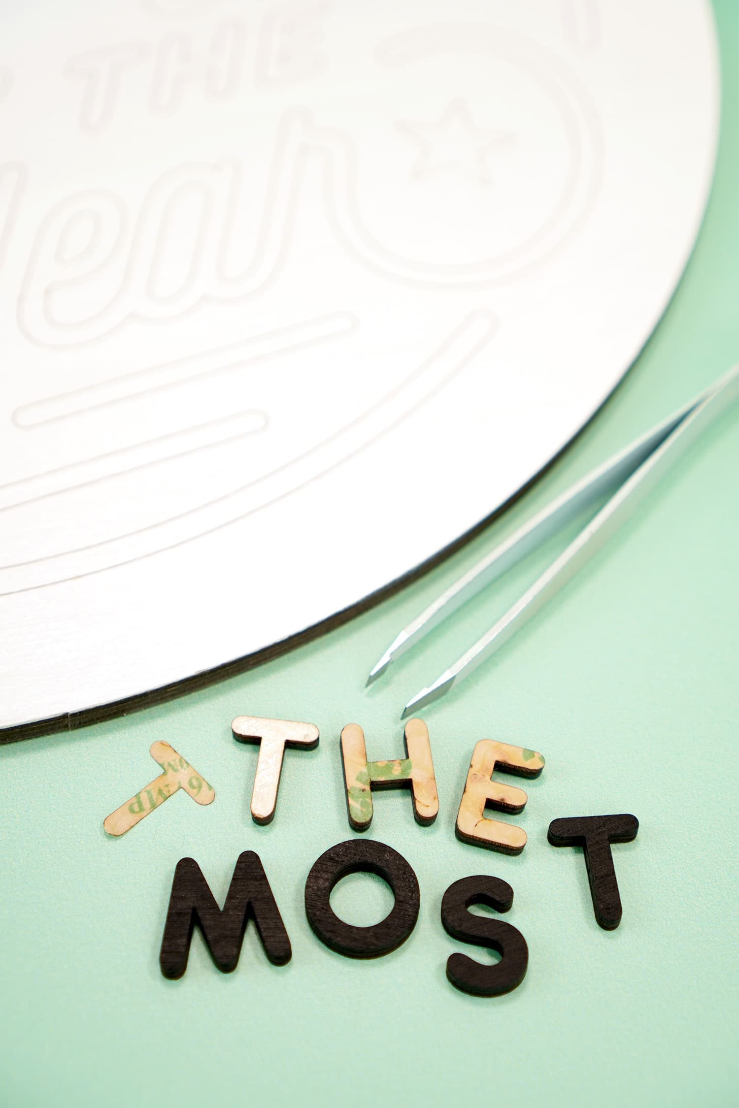 "Close up of ""The Most"" laser cut wood sign pieces and tweezers on mint green background"