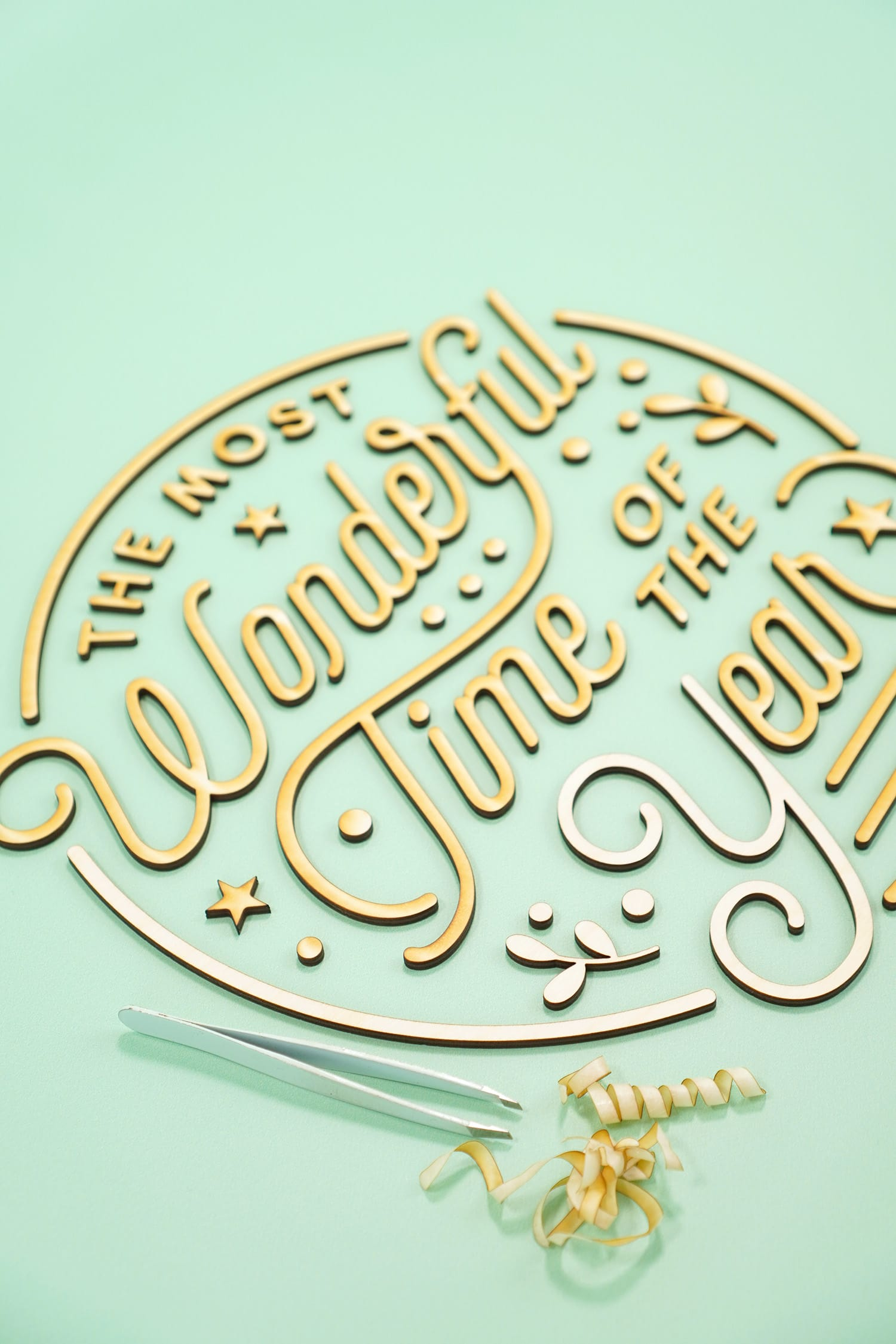 """The Most Wonderful Time of the Year' Laser Cut Wood Sign pieces with tweezers and pile of unmasked masking paper tape on mint green background"