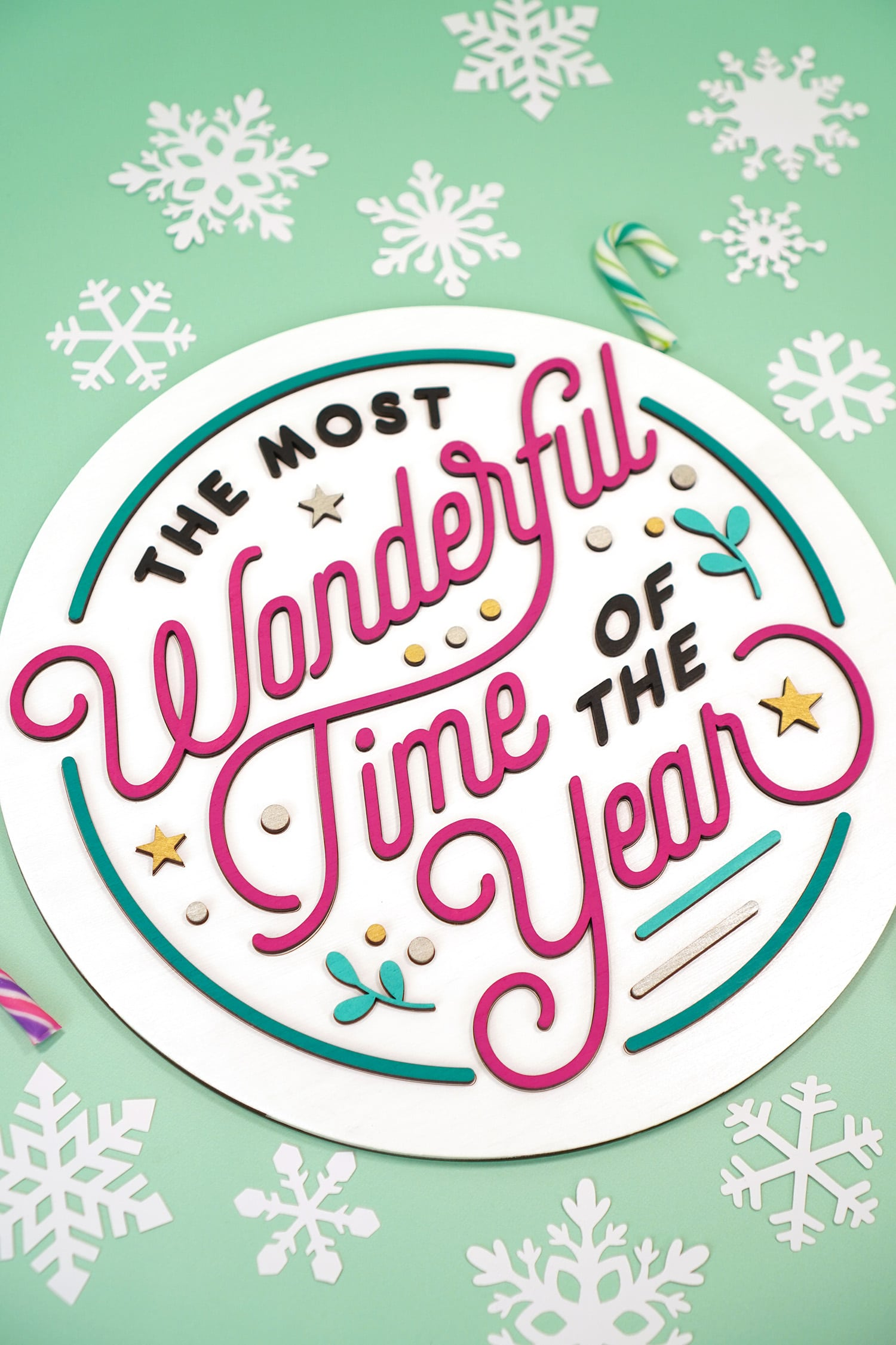 """The Most Wonderful Time of the Year"" Laser Cut Wood Sign on mint green background with paper snowflakes and candy canes"