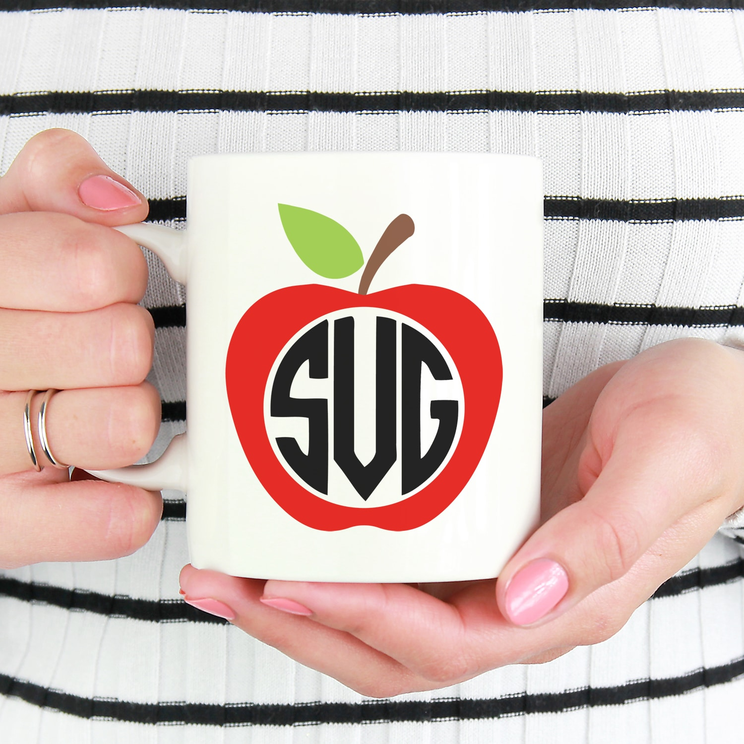 Close up of hands holding white mug with red apple design and monogram SVG