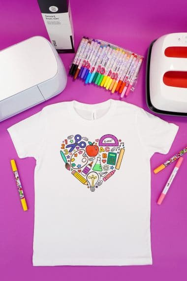 Back to school coloring shirt on a purple background surrounded by fabric markers and Cricut supplies