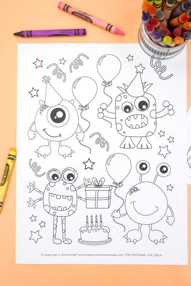 Monster coloring page with birthday party theme on an orange background with crayons